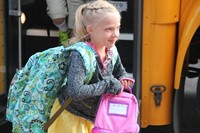 girl smiles walking toward first day of school