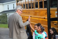 principal jim pritchard gives student a high five getting off the school bus