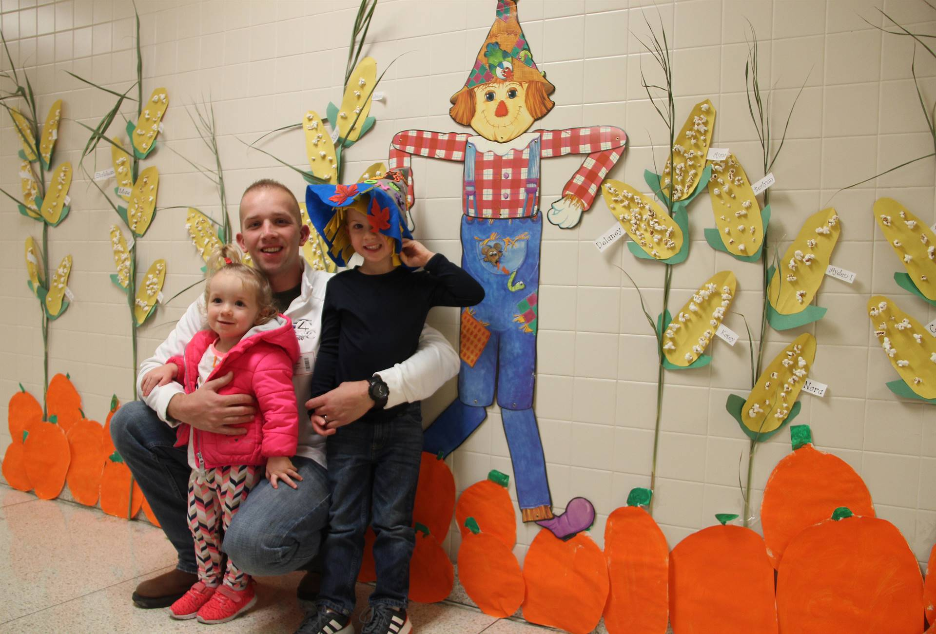 student and family members near scare crow decorations