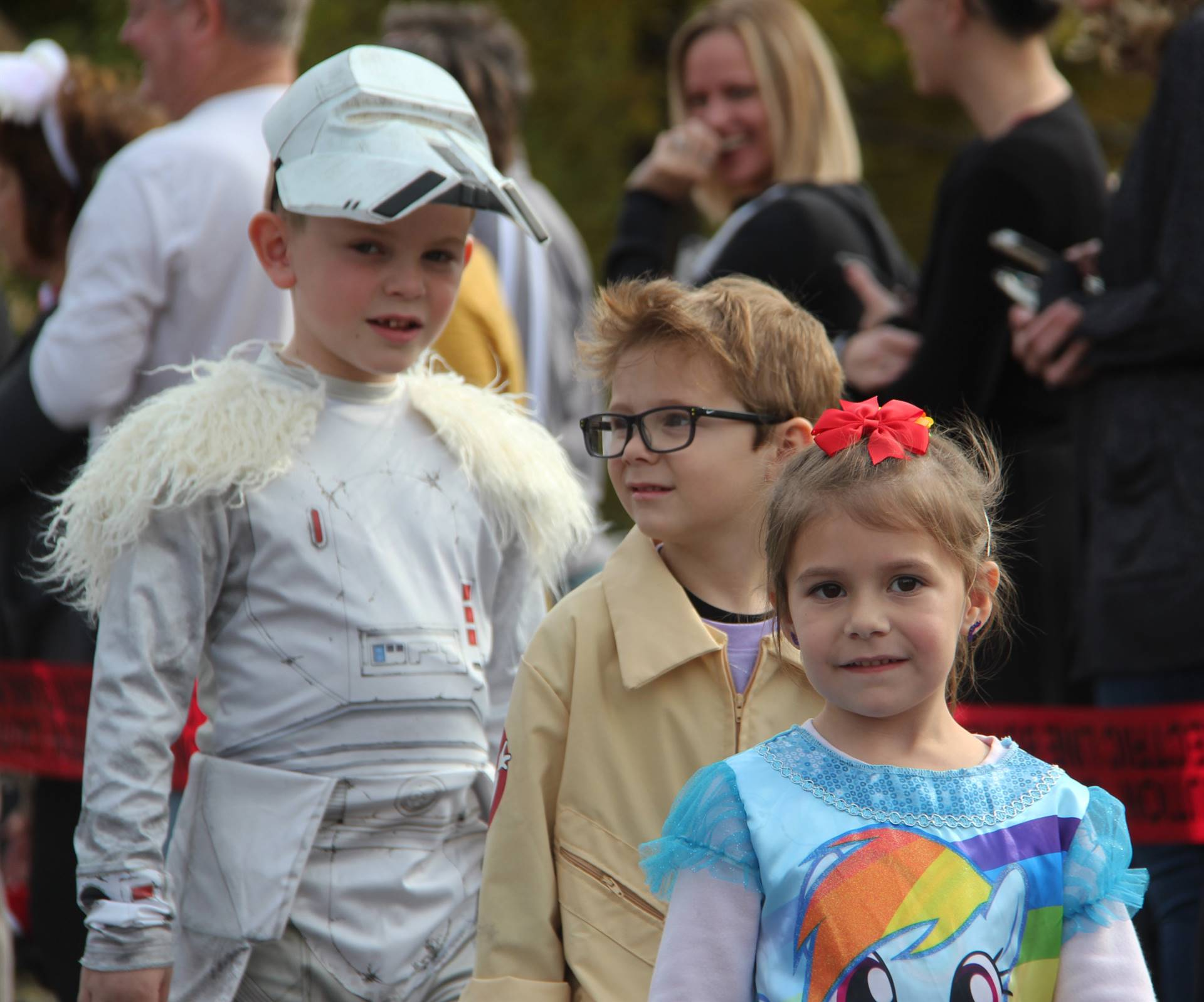 three students wearing halloween costumes