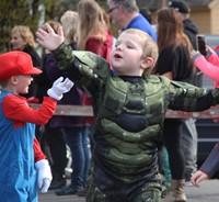 students waving wearing halloween costume