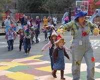students and teacher parading wearing scare crow hats