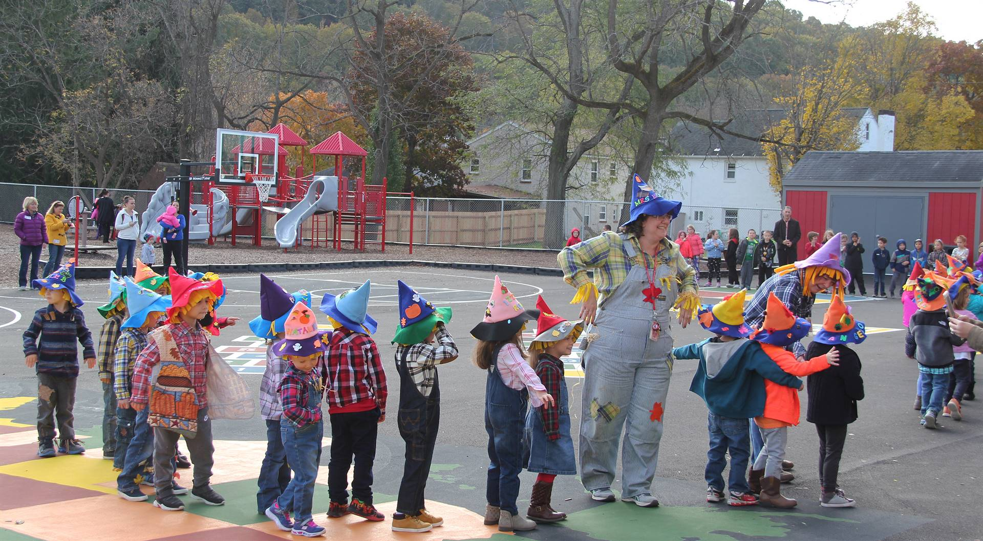 students and teachers parading in scare crow hats
