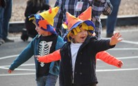 student waving wearing scare crow hat