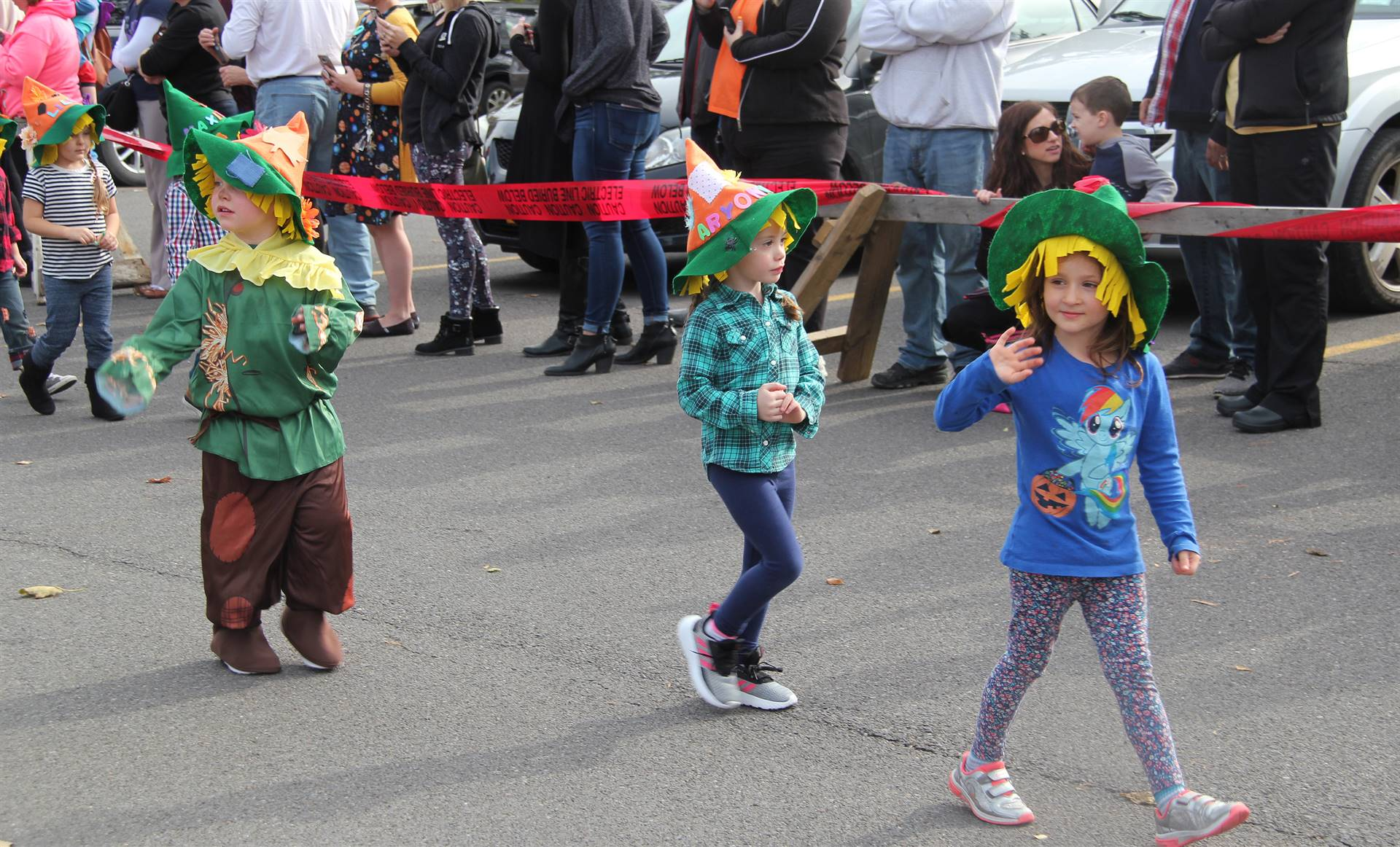 three students parading wearing scare crow hats