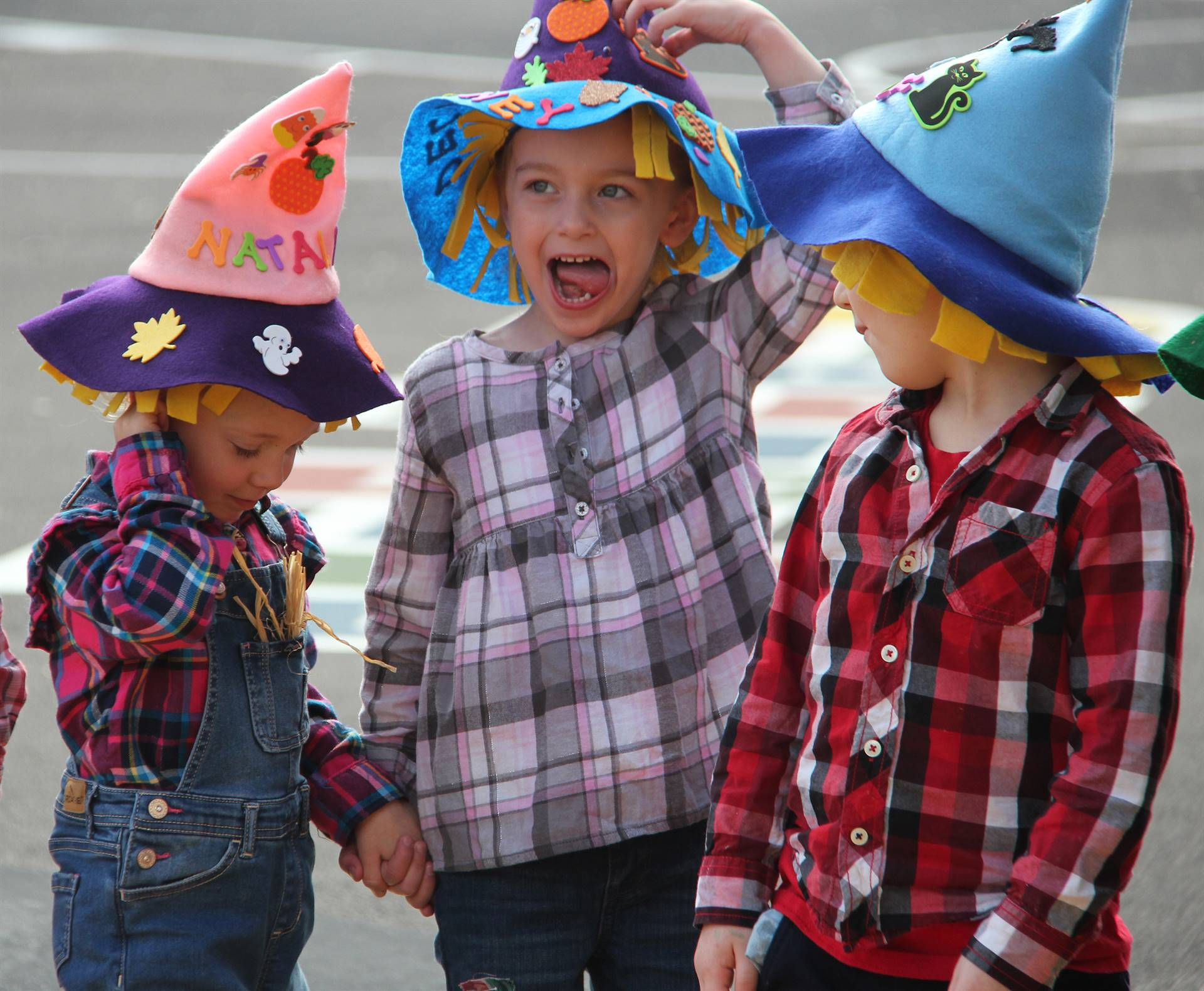 three students wearing scare crow hats
