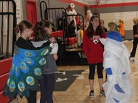 students being mummified at halloween event