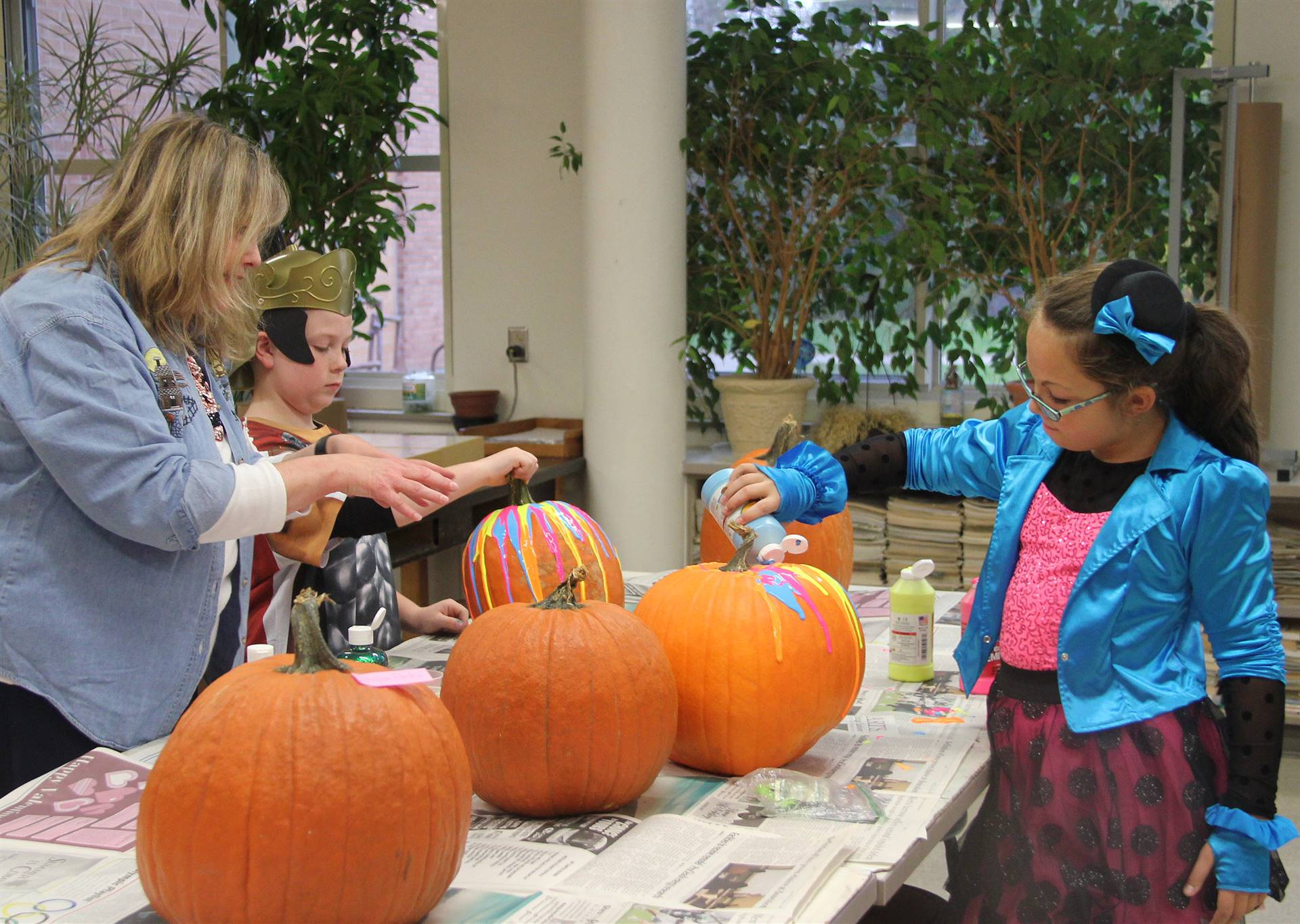 students and teacher painting pumpkins