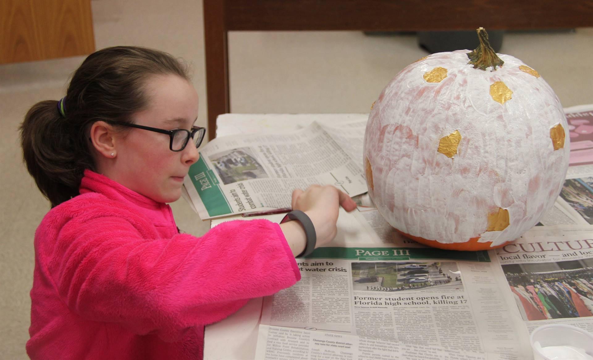 student painting pumpkin