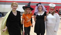 four students wearing halloween costumes