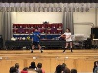 two students dancing on stage