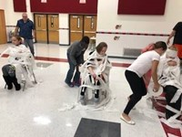 students mummifying students with toilet paper