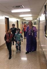 students and teacher walking down hall in costumes