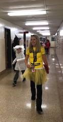 teacher and students wearing costumes walking down hall