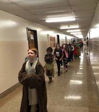 students wearing costumes walking down hallway