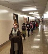 students wearing costumes walking down hallway