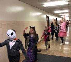 students and teacher wearing costumes walking down hallway
