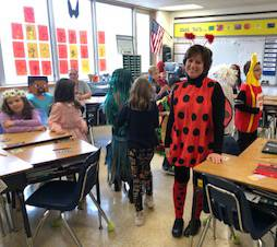students and teacher wearing halloween costumes in classroom