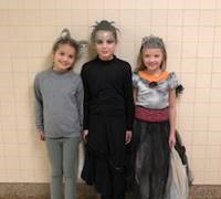 three students dressed in halloween costumes