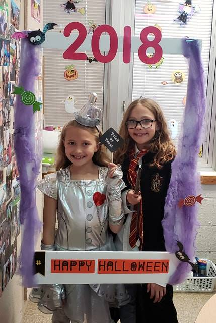 two students in costume with photo sign