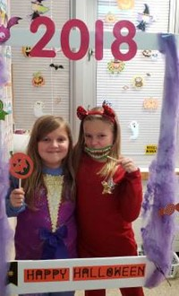 two students in costume at photo booth sign