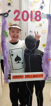 two students wearing costumes at photo booth sign