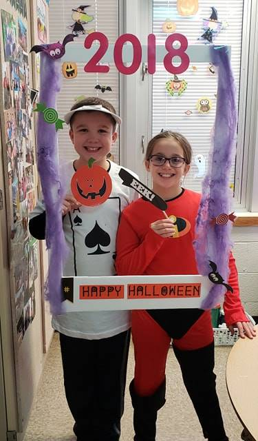 two students wearing costumes at photo booth sign in classroom