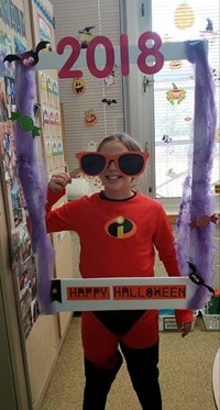 student wearing costume at photo booth sign