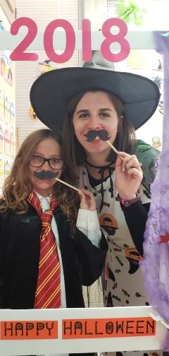student and teacher in halloween costumes with photo booth sign