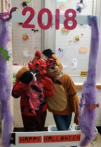 two students in costume at halloween photo booth sign