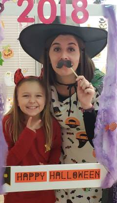 student and teacher in costume at halloween photo booth sign