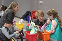 teachers and students at activity station