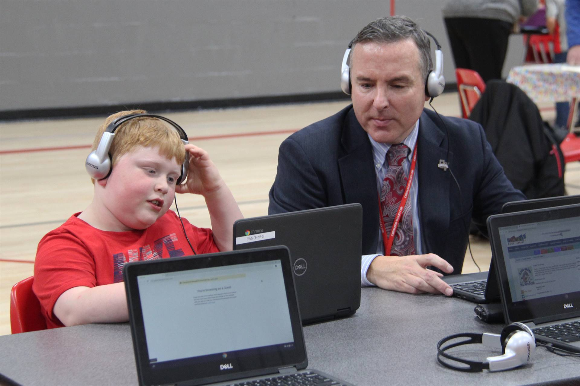 superintendent and student working on lap top computers
