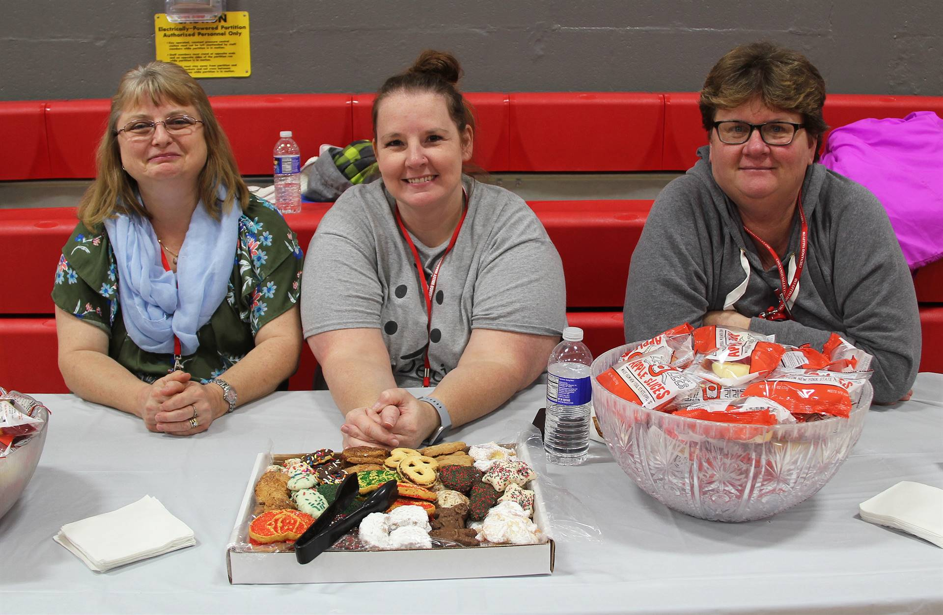 three people smiling at snack table