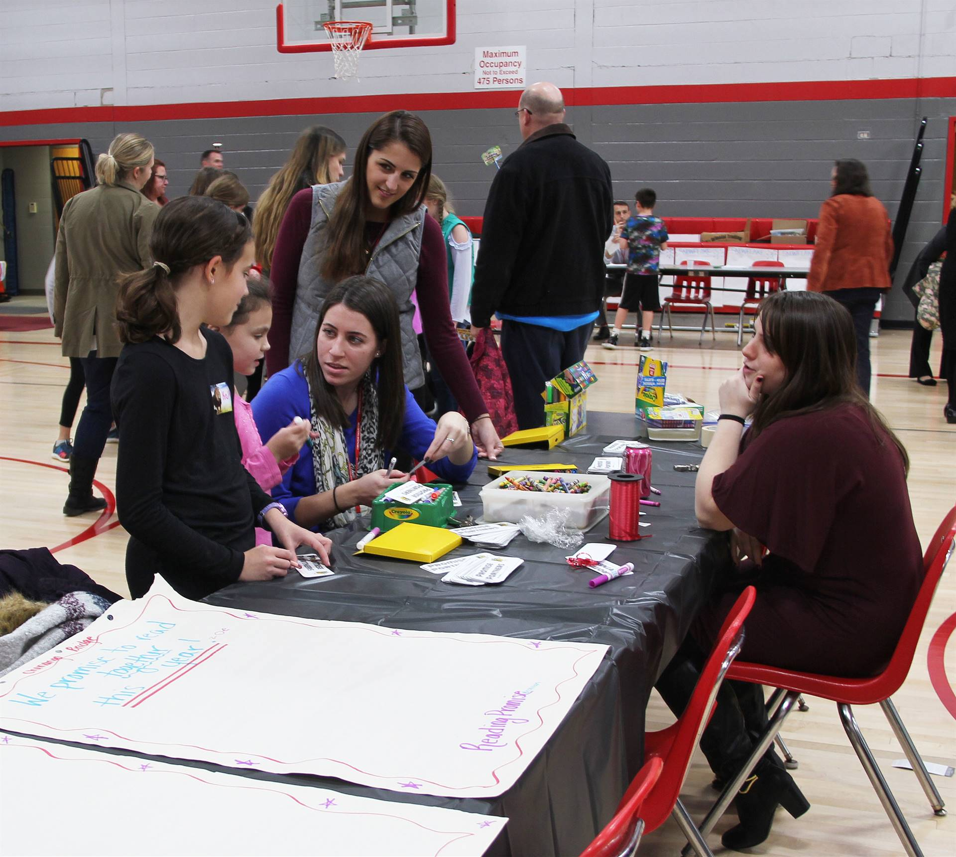 students and teachers at activity table