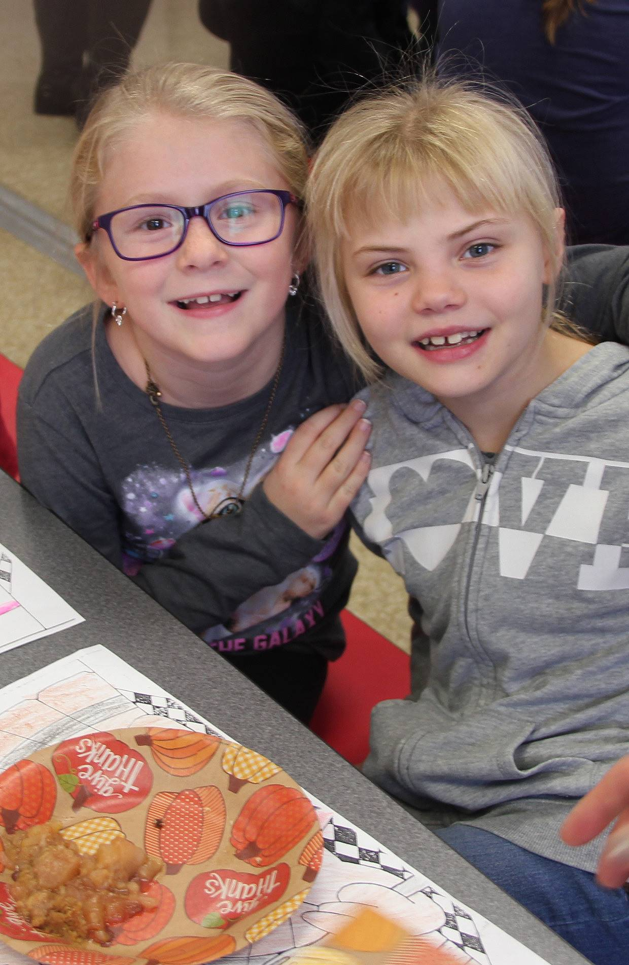 two students smiling at table