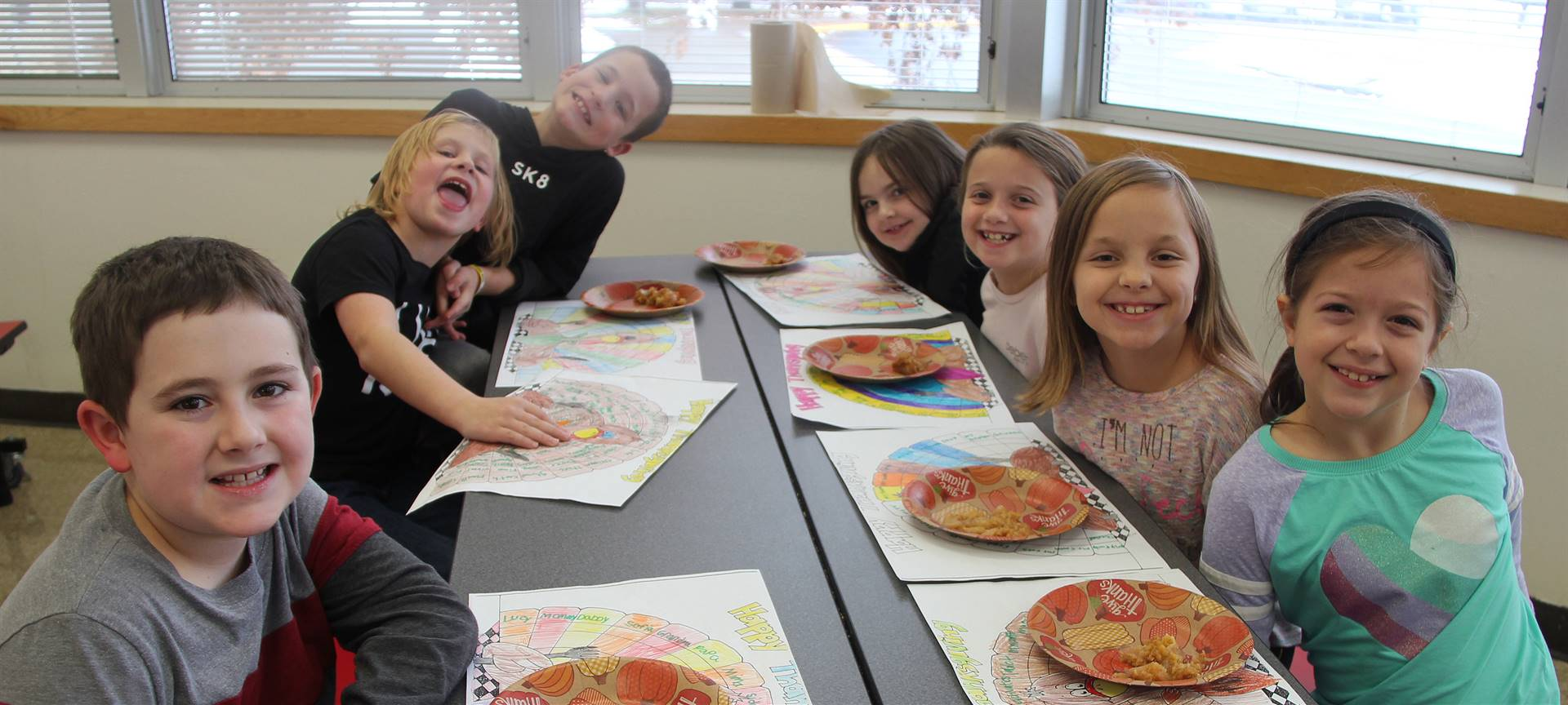 students smiling at cafeteria table