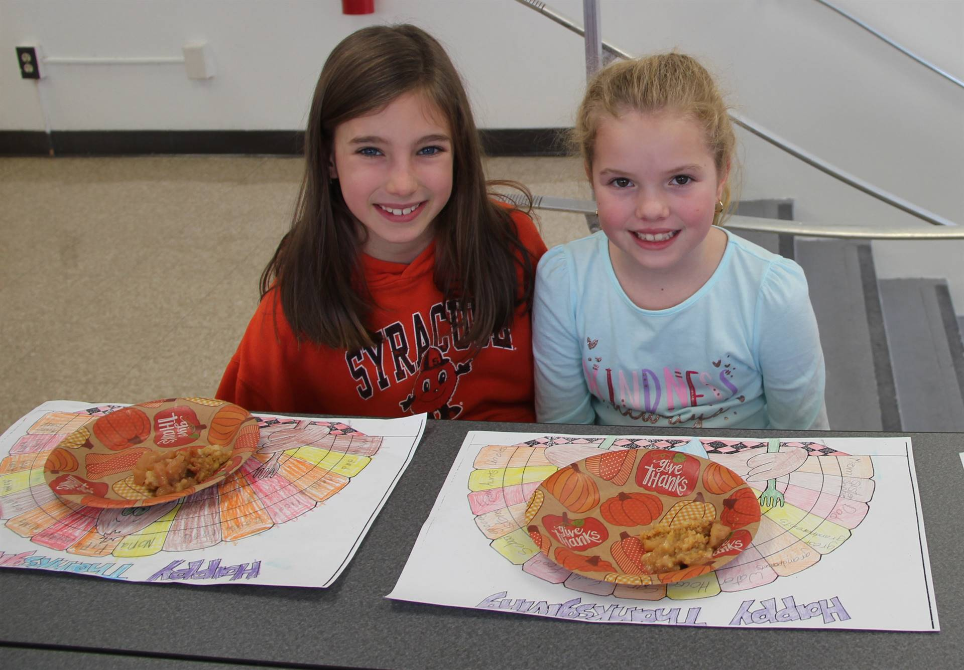two students smiling with thanksgiving treats