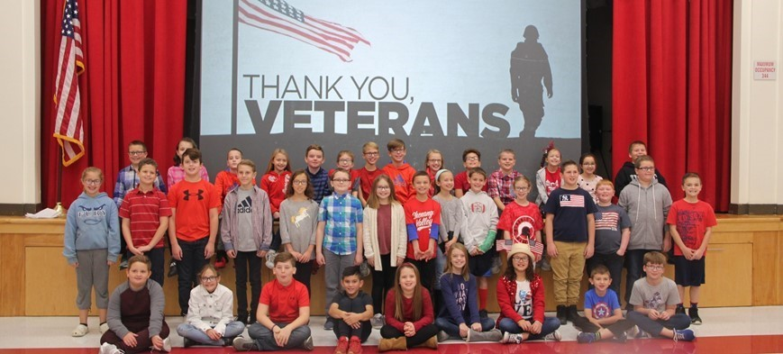 students next to thank you veterans sign