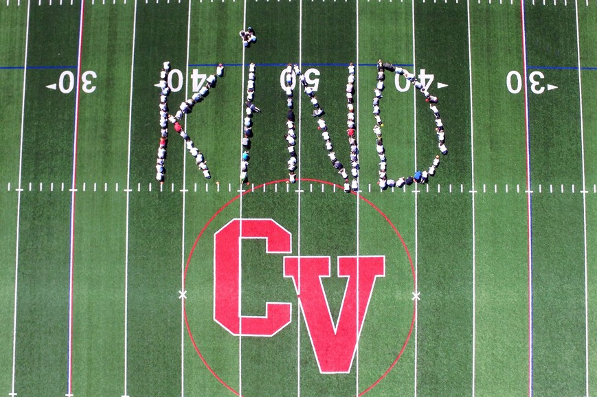 sixth grade students spelling out word kind on stadium field