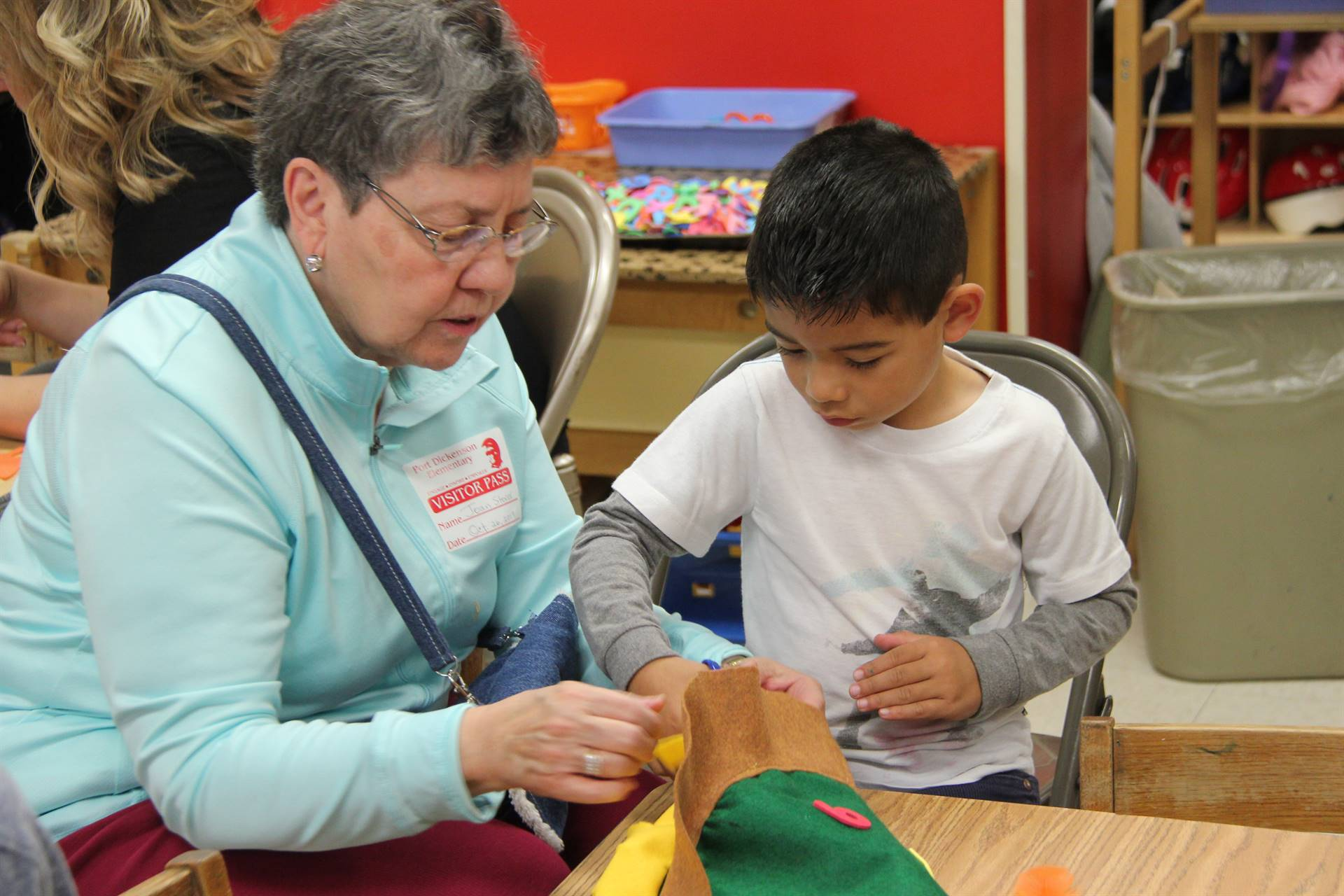 family member helping pre k student make a scarecrow hat