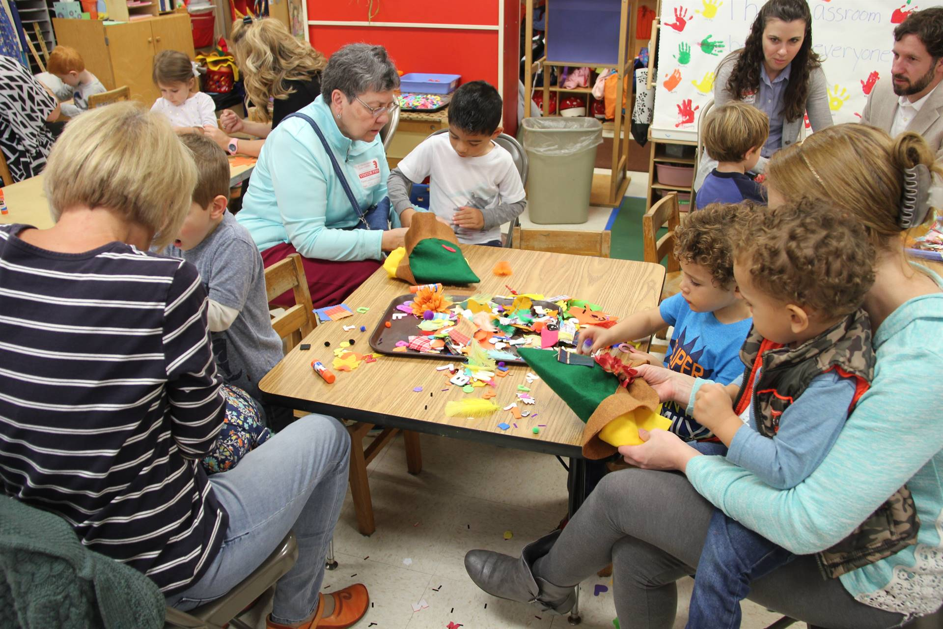 family members helping pre k students make scarecrow hats