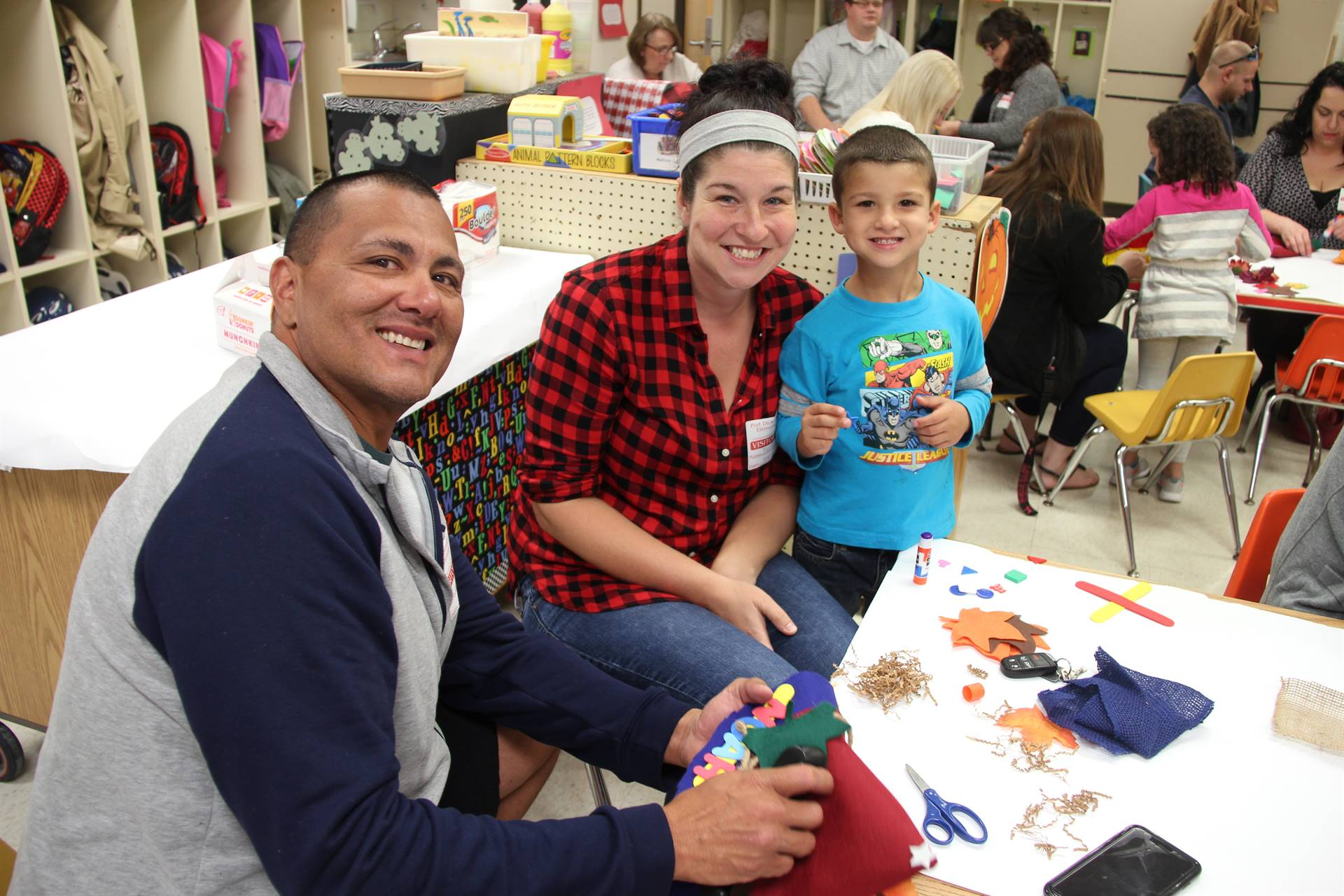 man and woman smile with boy at pre k family day