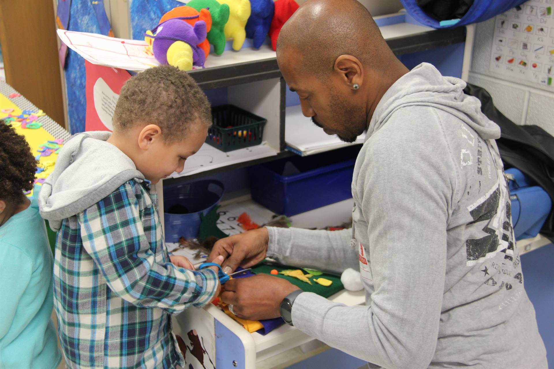 man helping student to cut a felt scarecrow hat