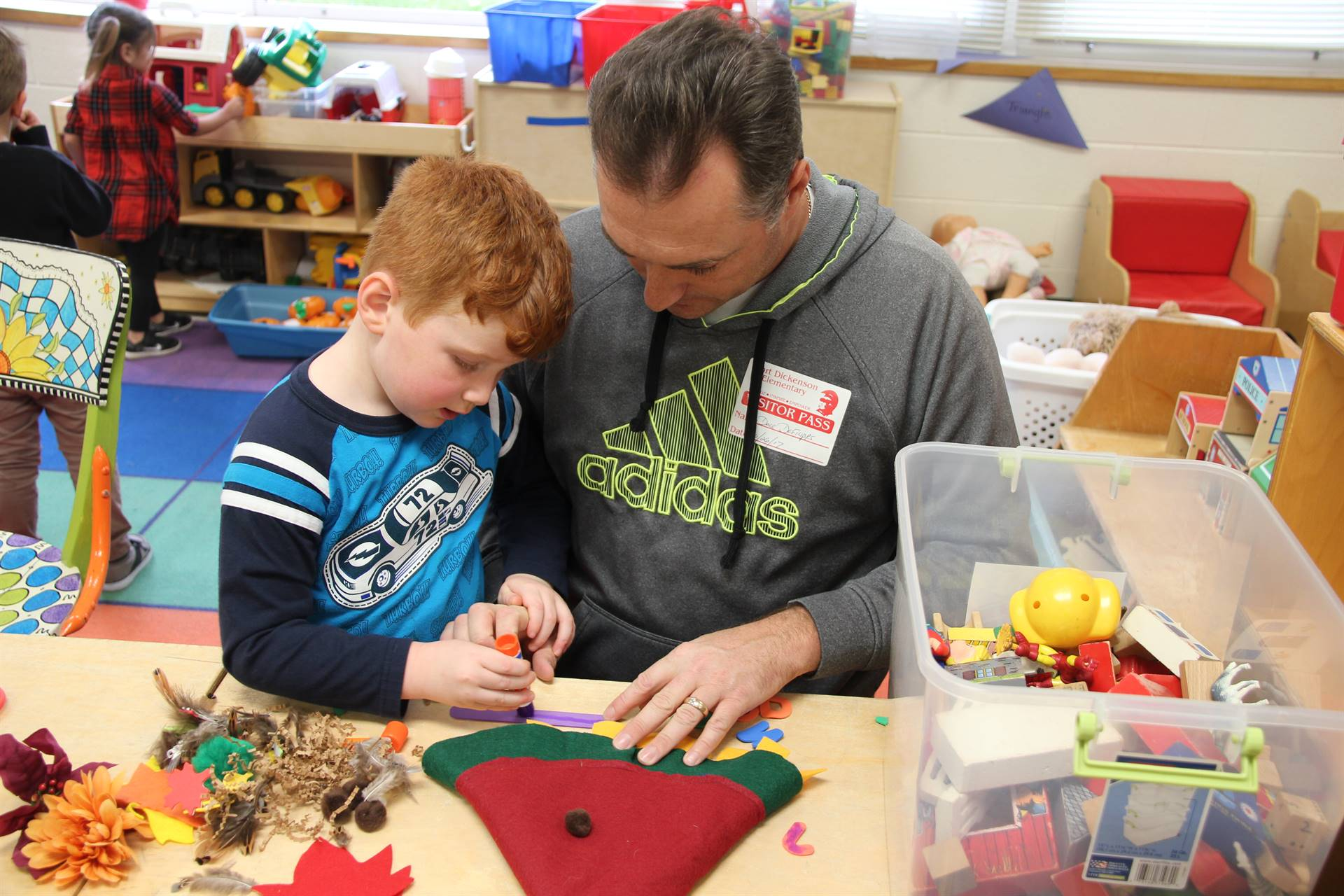 man helps boy make a scarecrow hat at pre k family day