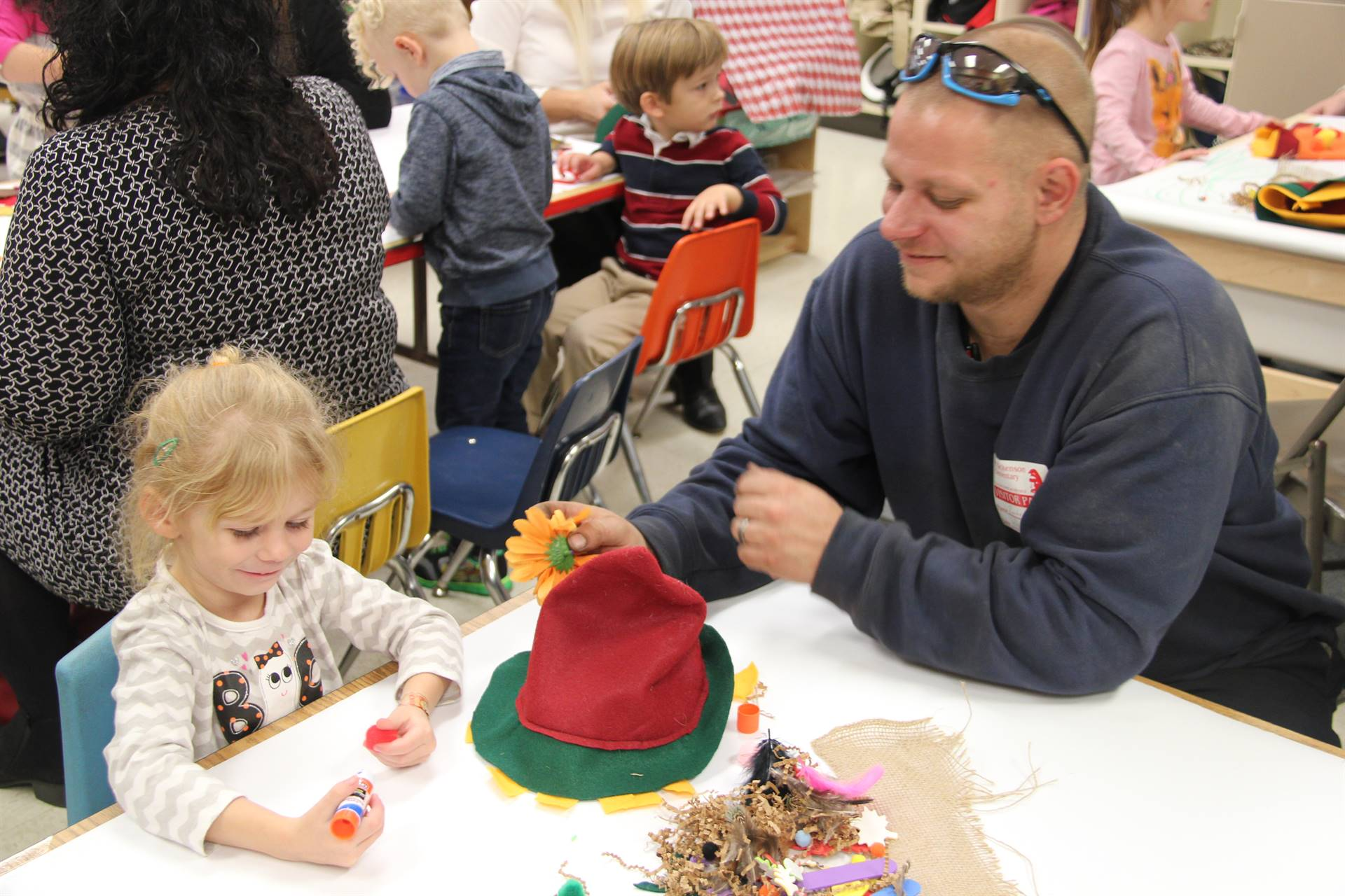 man helps student glue flower on hat at pre k family day