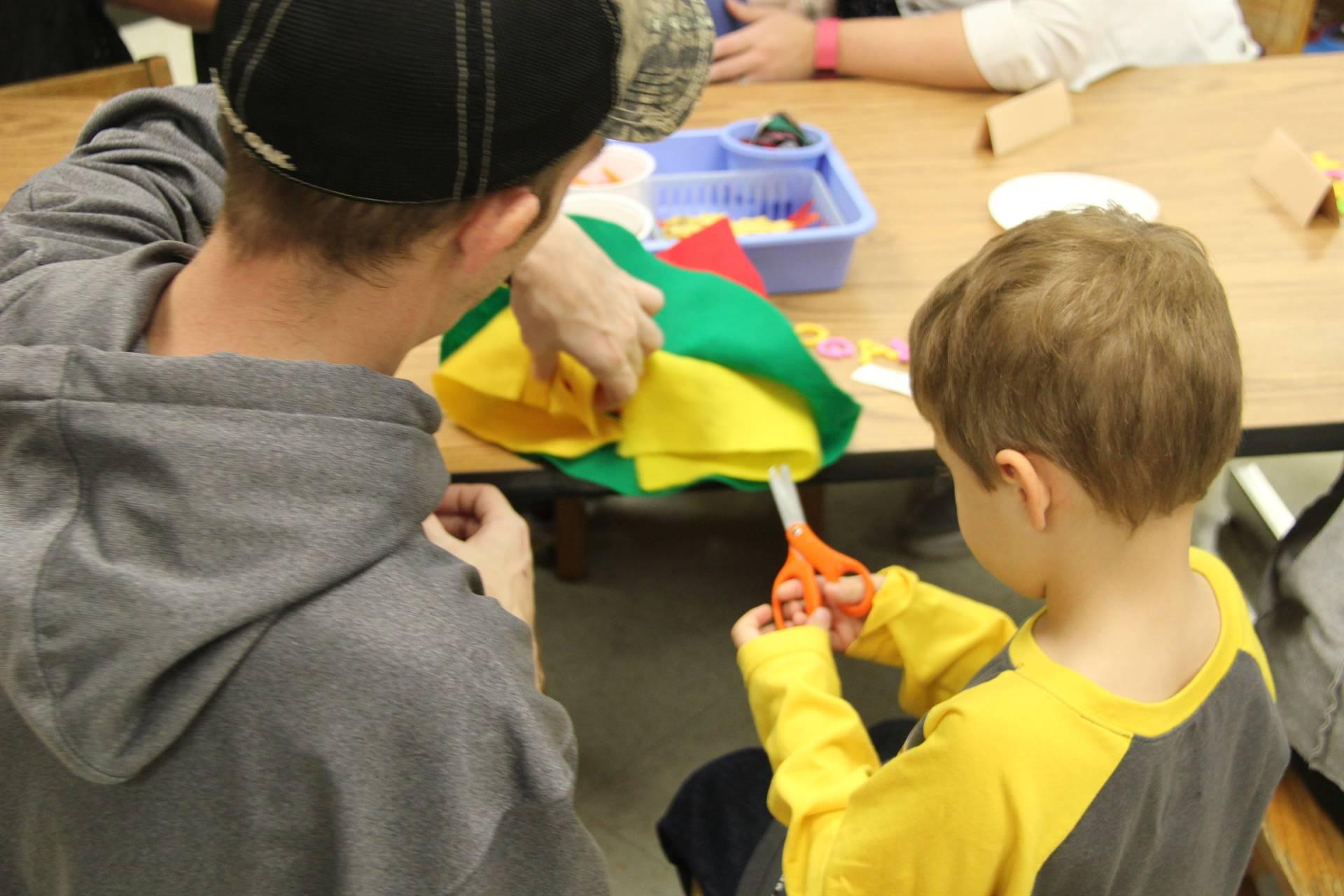 man helping boy cut scarecrow hat
