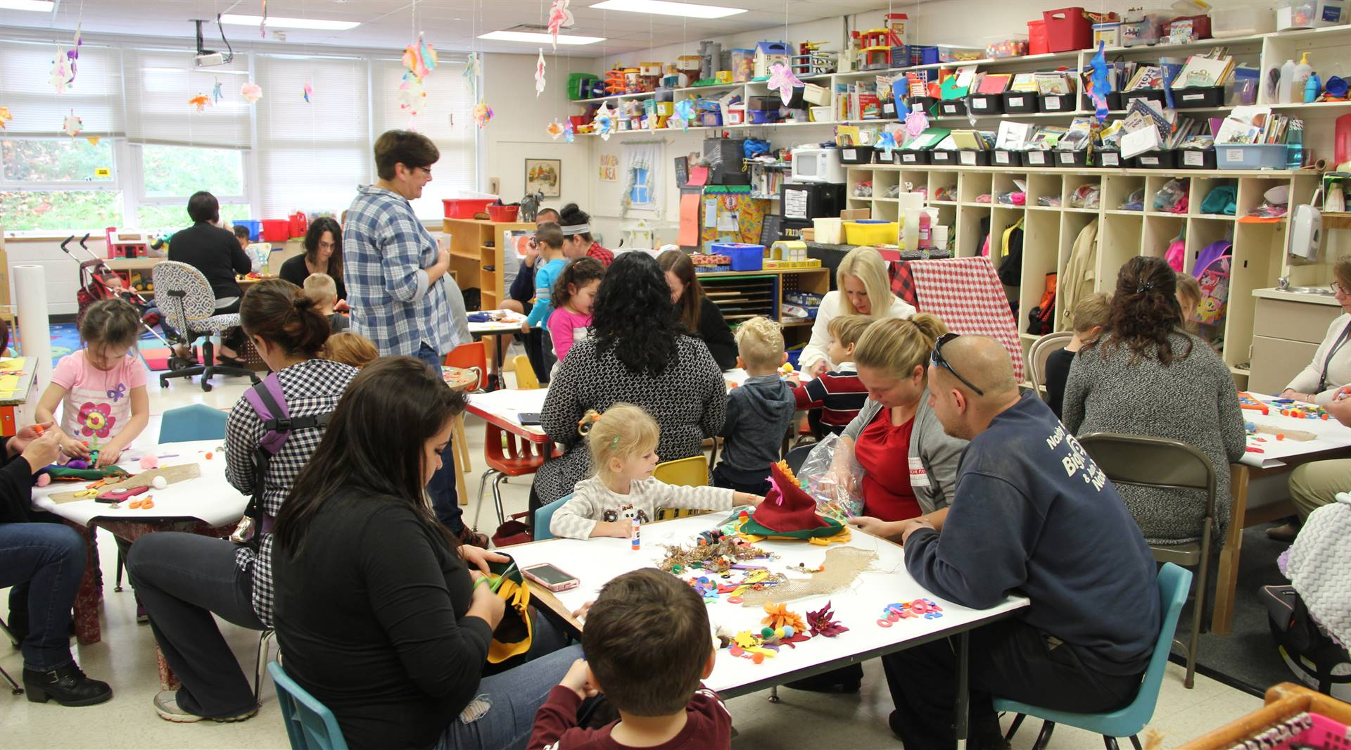 pre k classroom full of families making scarecrow hats