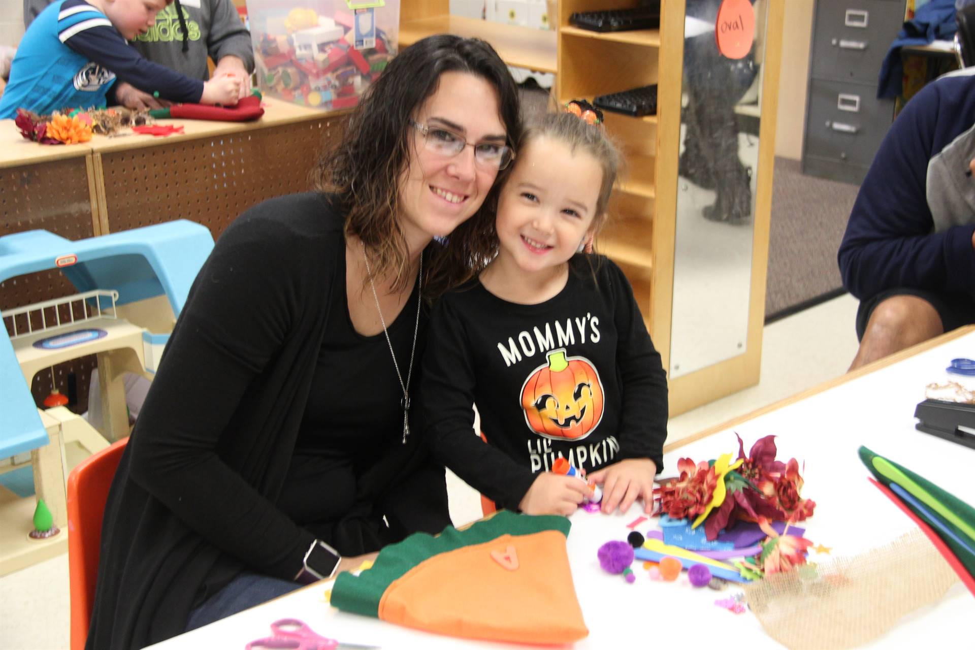 woman and student smile at pre k family day