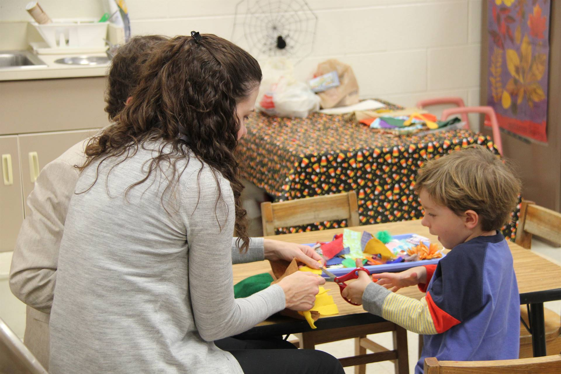 woman helping child to cut felt scarecrow hat